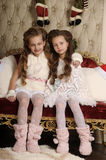 Two girls sisters in a Christmas interior Royalty Free Stock Photos