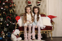 Two girls sisters in a Christmas interior Royalty Free Stock Images