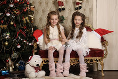 Two girls sisters in a Christmas interior Royalty Free Stock Photo