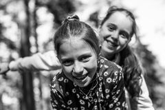 Two girls sisters or girlfriends having fun outdoors. Black and white photo stock images