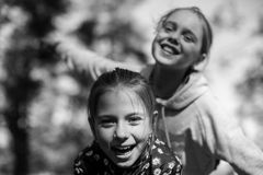 Two girls sisters or girlfriends having fun outdoors. Black and white royalty free stock photos