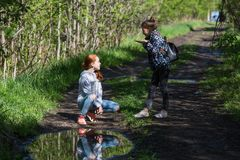 Two girls sisters or girlfriends are talking emotionally in the Park. Walking. stock photo