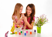 Two girls - sisters having fun painting Easter eggs Royalty Free Stock Image