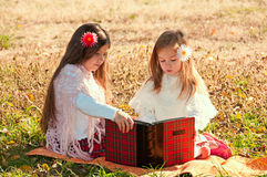 Two girls sisters read the book on the grass Stock Images