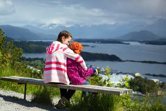 Two girls sisters. Sitting on a bench in the town of Alesund and the mountains to the fjord in the background, norway stock images