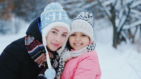 Two Girls Sisters Smiling. Two little girls sister smile at each other on the street in winter stock footage