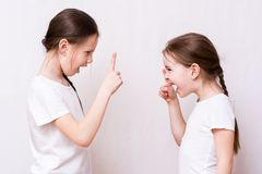 Two girls sisters strongly quarrel with each other stock photo