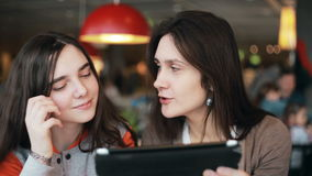 Two girls sisters using tablet talking in cafe. Two girls sisters using tablet computer touchscreen,  talking, laughing in cafe stock video footage
