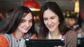 Two girls sisters using tablet talking in cafe. Two girls sisters using tablet computer touchscreen,  talking, laughing in cafe stock footage