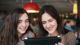 Two girls sisters using tablet talking in cafe. Two girls sisters using tablet computer touchscreen,  talking, laughing in cafe stock video