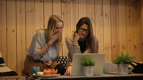 Two girls sit in cafe and looking at a laptop stock footage