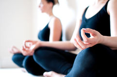 Two Girls Sit Cross Legged in a Yoga Pose Stock Images