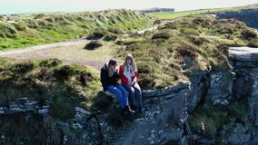 Two girls sit on the edge of the famous Cliffs of Moher in Ireland. Travel photography stock video