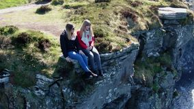 Two girls sit on the edge of the famous Cliffs of Moher in Ireland. Travel photography stock footage