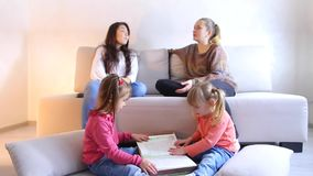 Two girls sit on floor and flip book, young moms sit on sofa next to and discuss problem. Two children sit on floor in living room and flip through interesting stock footage
