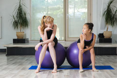 Two girls sit on gymnastic balls in gym Stock Photo