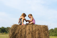 Two girls sit on haystack Stock Images