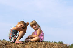 Two girls sit on haystack Stock Photos