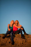 Two girls sit hugging and laughing at the blue sky Royalty Free Stock Photos