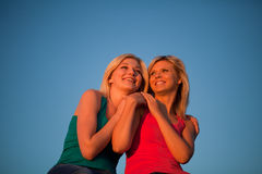 Two girls sit hugging and laughing at the blue sky Royalty Free Stock Photo