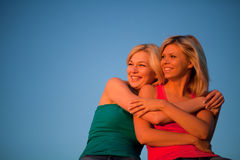 Two girls sit hugging and laughing at the blue sky Stock Photo