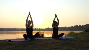 Two Girls Sit on Mats in Semi-Lotus Pose on a Lake Bank at Sunset in Slo-Mo. Two Slim Women Sit on Mats in a Semi-Lotus Pose, Raise Their Arms Up, Relax, on a stock video
