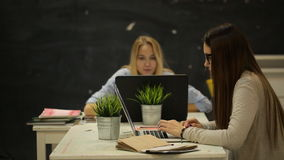 Two girls sit in the office and talking. Two smilling businesswomen working on laptop at office and smilling stock footage