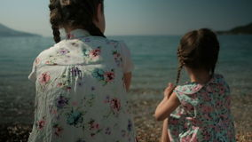 Two girls sit on the shore and throw stones into the water. Two pigtails are braided on the head of the sisters. Dressed babes in dresses with floral print. In stock video footage