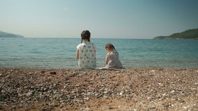 Two girls sit on shore and throw stones into water in summer day outdoors. Children Little sisters with pigtails dressed in colorful attire, rest on stock video