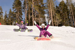 Two girls sit on the ski slopes Stock Images