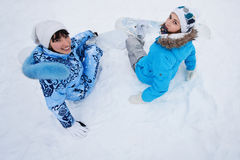 Two girls sit on snow and preparing to ride Stock Photography