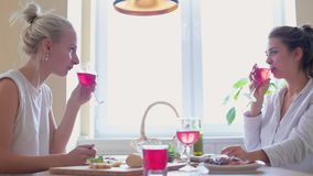 Two girls sit on a table in the kitchen talking and drinking.  stock footage