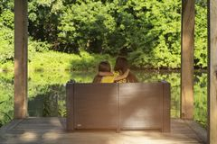 Two girls sit on a warm day on the river bank, hugging each other. stock images