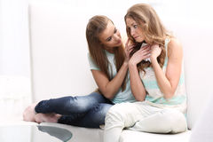 Two girls sitting on. The couch Stock Photography