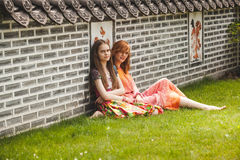 Two girls sitting at ancient korean park against brick wall Royalty Free Stock Photography