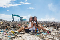 Two girls sitting back to back at garbage dump Royalty Free Stock Photography