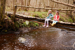 Two Girls Sitting On Bridge Fishing In Stream With Net Stock Photos