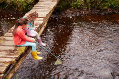 Two Girls Sitting On Bridge Fishing In Stream With Net Stock Images