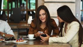 Two girls sitting in a cafe looking at the phone and discuss what they saw. A guy comes up and shows a funny picture on. His teelphone stock footage