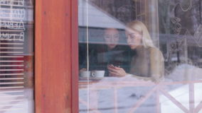 Two girls sitting in cafe and looking at the phone. stock video footage