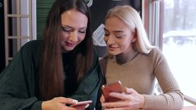Two girls sitting in a cafe with a phone in hand. stock video