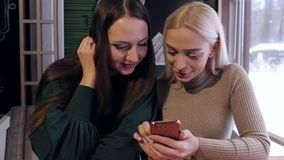 Two girls are sitting in a cafe with phones. stock video footage