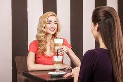 Two girls sitting in cafe and talking. Royalty Free Stock Photos