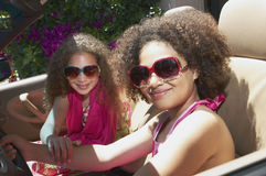 Two girls sitting in a car. A pair of mixed race young girls wearing sunglasses sitting inside a car Stock Image