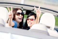 Two girls sitting in the car and gesturing victory sign. Two happy girls sitting in the car and gesturing victory sign look back and have fun while having little Stock Image