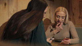 Two girls are sitting in a dark cafe with phones. stock video