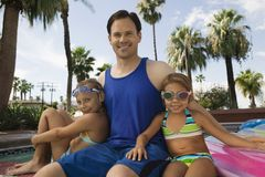 Two girls (7-9) sitting with father by pool portrait. Stock Image