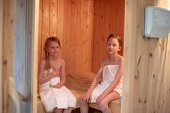 Two girls are sitting in a Finnish sauna stock image