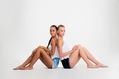 Two girls sitting on the floor Royalty Free Stock Photos