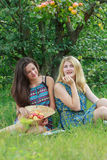 Two girls sitting on garden grass under tree branch with apples Royalty Free Stock Image